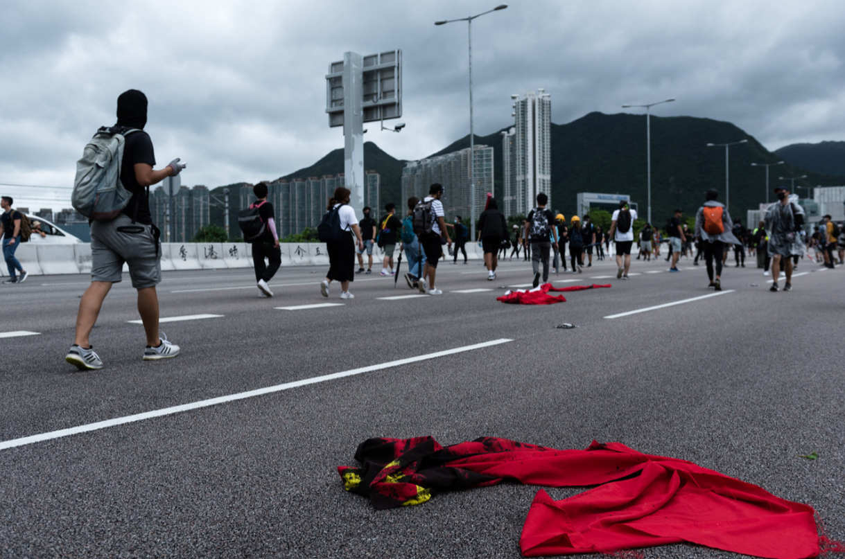 Protestors walk past defaced Chinese flags.